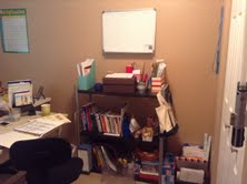 This bookshelf is holding the Sonlight curriculum and some supplies. To the left is my work area.