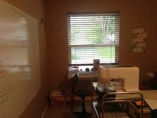 Against the window is Briana's desk and on the wall to the left is our whiteboard which measure 6x4.
